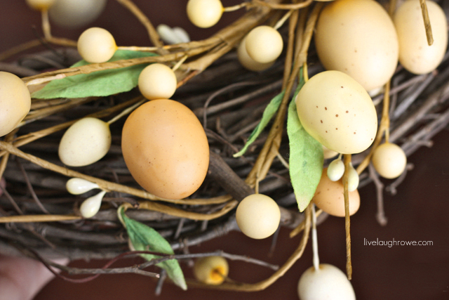 intertwine the egg garland within and around the grapevine wreath.