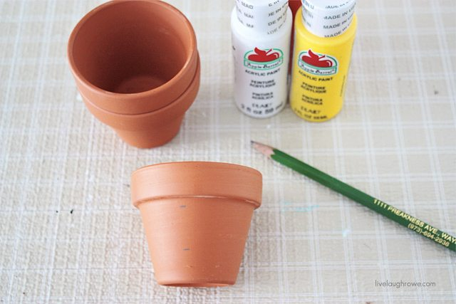 DIY Painted Cand Corn Pots.  First step is to determine where you want your stripes...