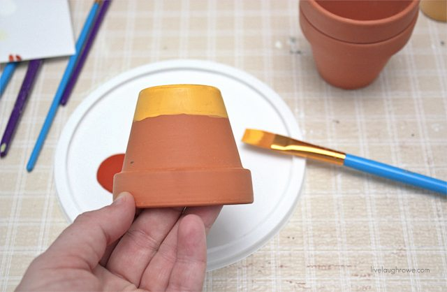 DIY Painted Candy Corn Pots. Second step is to start painting your stripes!