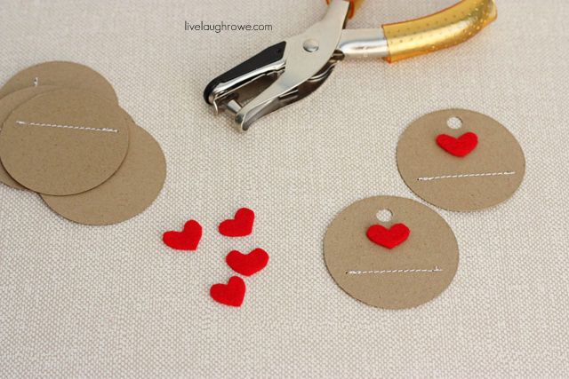 After stitching a line, punch a hole into label and attach heart with glue