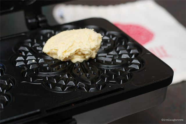 placing pizelle batter onto the hot griddle