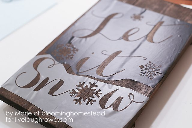 Stenciling on the text for woodland sign.
