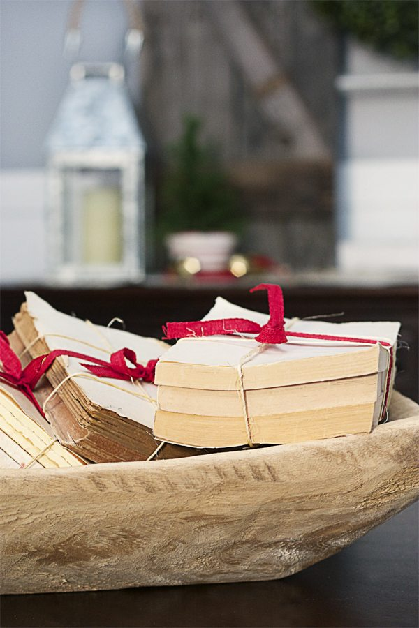 A bowl filled with old coverless books wrapped in red ribbon makes for a lovely holiday centerpiece.  www.livelaughrowe.com #holidaydecor