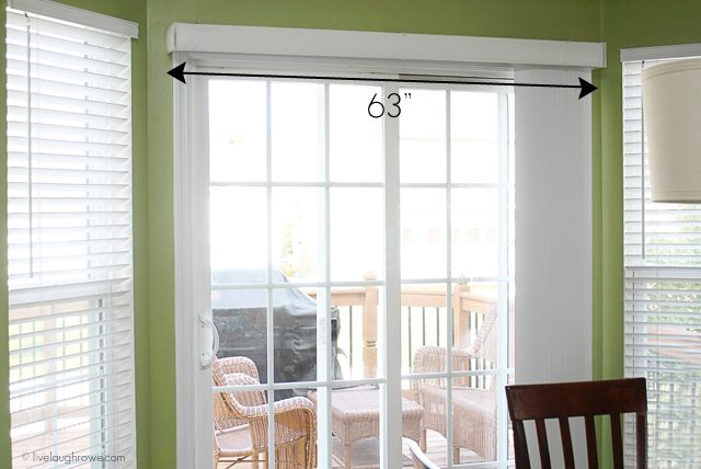 Measuring the sliding glass door area to prepare the build for our DIY Wood Cornice Box --- with attached curtain rod! www.livelaughrowe.com