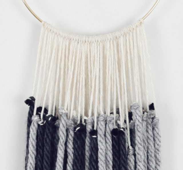 A DIY Yarn Tapestry tutorial. Create this beautiful macrame inspired wall hanging with yarn and a brass hoop. Just tie a few knots.