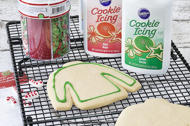 Outlining the ugly sweater sugar cookies!