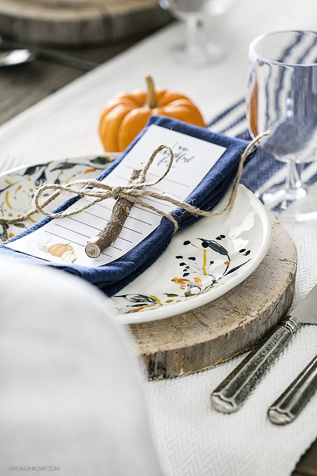 Blogger of livelaughrowe.com shares this simple fall tablescape with rustic flare and offers a free printable bookmark to use at each place setting.