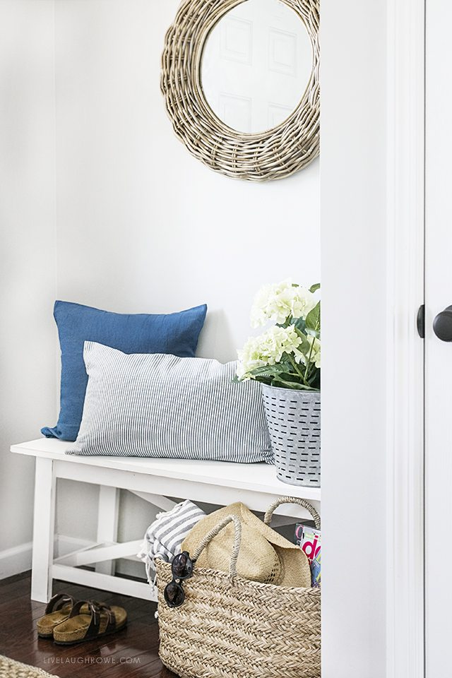 A simple summer entryway with shades of blue and seasonal flowers create a warm and welcoming space. livelaughrowe.com