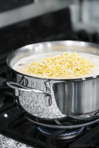 Cheese being added to White Chicken Chili Recipe being prepared in the Lagostina Opera Cookware. Recipe at livelaughrowe.com
