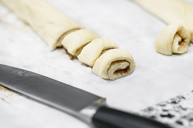 Rolling the dough and cutting the mini cinnamon buns.