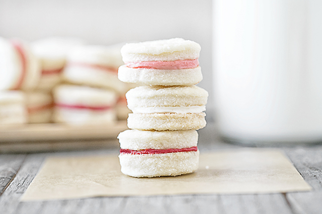 Meet your new favorite cookie! This Cream Wafer Cookie Recipe is packed with sweet, buttery crunchy goodness. Make the frosting with different colors for holidays and special events... like these with pink filling for Valentine's Day! Recipe at livelaughrowe.com